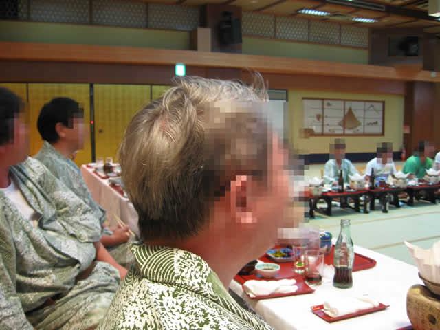 写真3:宴会の写真です。ホテルのお座敷に、たくさんの社員さんたちが宿浴衣を着て、お膳を並べて座ってます。お膳の上にはおいしそうな料理がいっぱいです。
