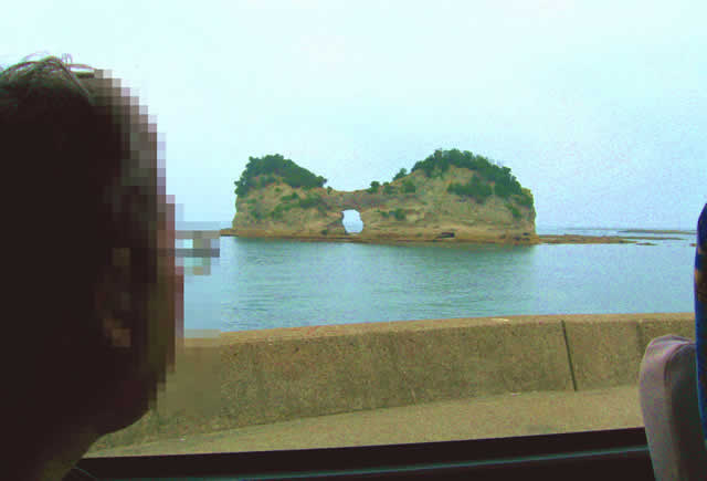 写真7:海に小さな無人島が浮かんでいます。波で侵食され、真ん中に丸い穴があいているので、穴をくぐって島の裏側へ行けそうなくらいです。まるでメガネのような形です。