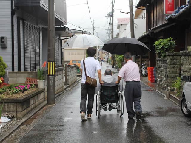 写真5:車椅子を押され、傘をさして、道幅3~4メートルほどの地区のメインストリートを歩く写真です。