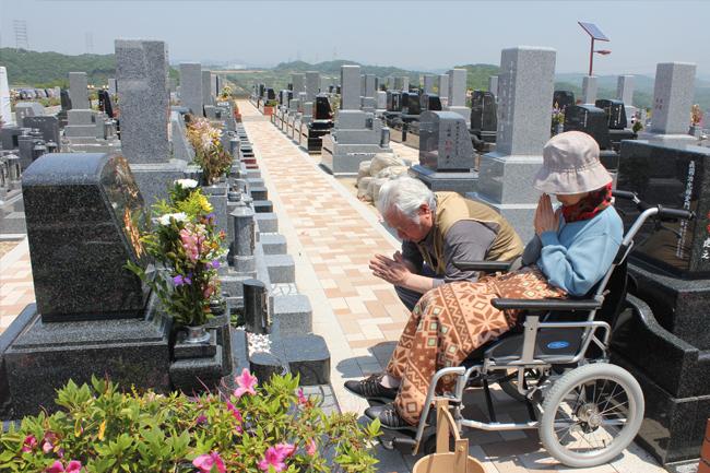 写真:お墓に手を合わせる二人。車椅子をお使いの奥さま。