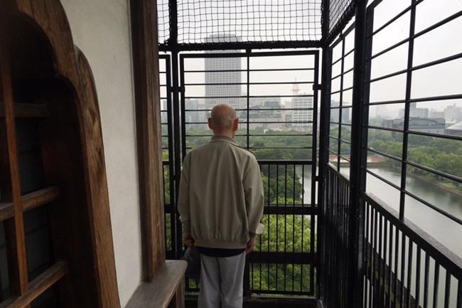 写真:広島城天守閣から街を眺めるお客様の背中