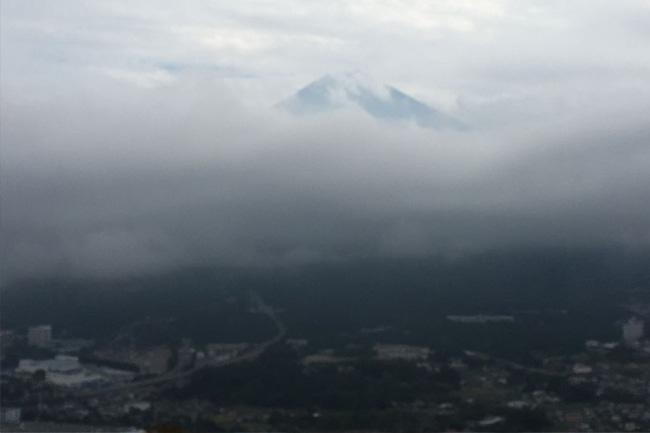 写真:雲の向こうにうっすらと見える富士山