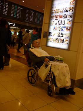 写真:空港の看板前で待機中