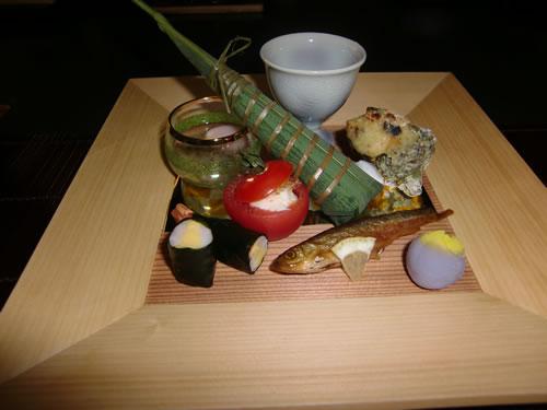 写真:前菜。木目の入ったお皿にさまざまな小鉢が並ぶ。