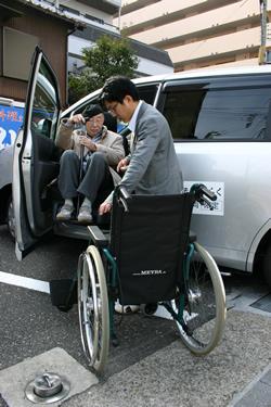 写真:タクシーから車いすに乗り込むお客様