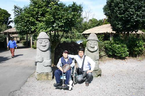 写真:済州島の像、トルハルバンの前でエスコートヘルパーと記念撮影