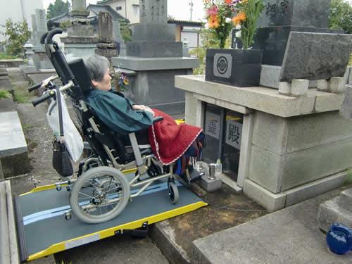 写真:車椅子に乗り、お墓の前で手を合わすお客様