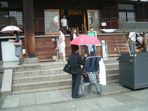 写真:弟様ご夫妻に傘をさしてもらいながら拝む
