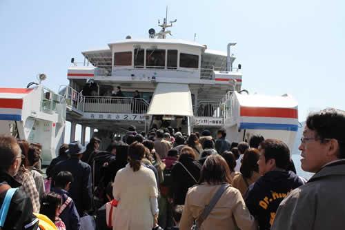 写真:大勢の観光客とともにフェリーに乗り込む